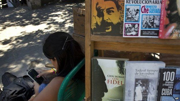 A street vendor plays with her smartphone while selling books about the Cuban revolution