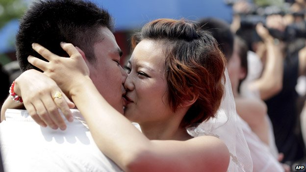 This picture taken on August 13, 2013 shows newly-married couples kissing each other at their wedding ceremony at the Happy Valley theme park in Wuhan in central China's Hubei province, on the Chinese traditional Qixi Festival, known as the 'Chinese Valentine's Day'. The festival dates back over 2,600 years and is a popular and auspicious wedding date for Chinese couples.