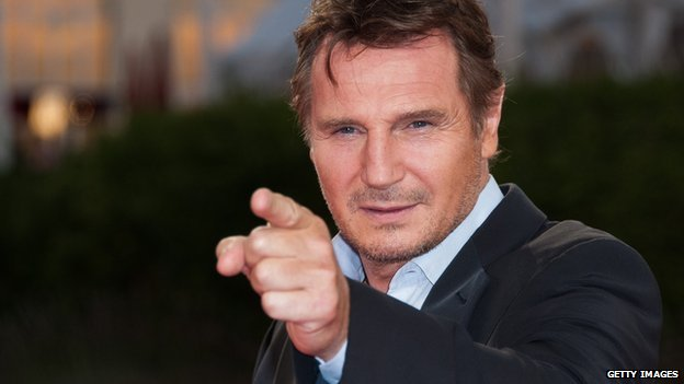 Liam Neeson points at the camera in a 2012 photo.
