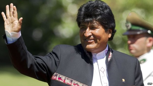 Bolivia's President Evo Morales waves at the press in Chile on March 11, 2014.