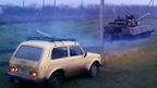 Still from unverified amateur footage purportedly showing Lada car chasing tank