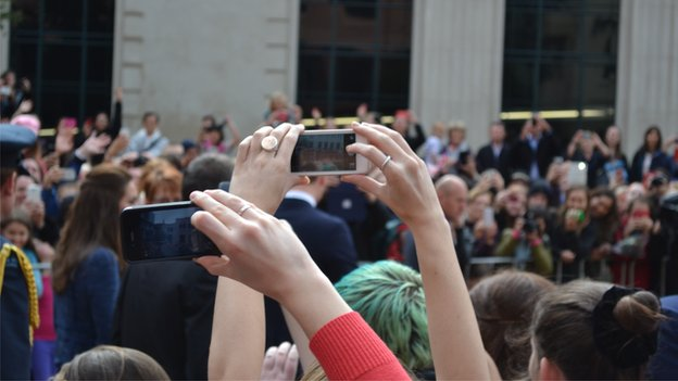People try to take photos of the royals after the sun came out just in time for William and Kate to walk through Civic Square, before heading to Wellington Airport