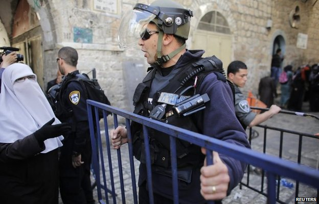 An Israeli policeman holds a barrier as he stops a Palestinian woman from entering the Haram al-Sharif/Temple Mount compound (16 April 2014)