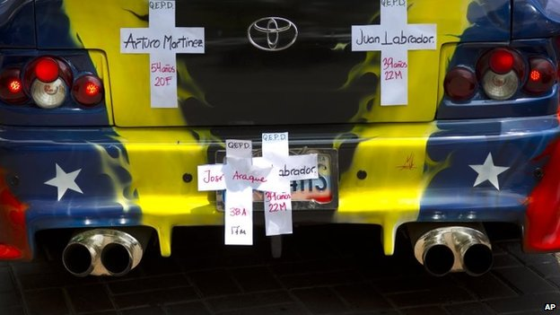 Several crosses with the names of people killed during the protests hang in a car decorated with the Venezuelan flag during a march of remembrance for those fallen during the protests, in Caracas, Venezuela, Tuesday, April. 15, 2014.