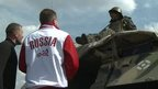Man in 'Russia' jacket stands in front of military vehicle