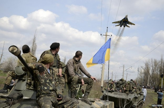 Ukrainian soldiers watch a jet pass near Kramatorsk, Ukraine, 16 April