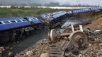 A rescuer climbs into a compartment at the scene of a derailed train at Teghria village near Jagiroad Rail Station