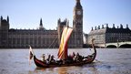 "People dressed as a ""Viking warrior-crew"" sail along the River Thames"