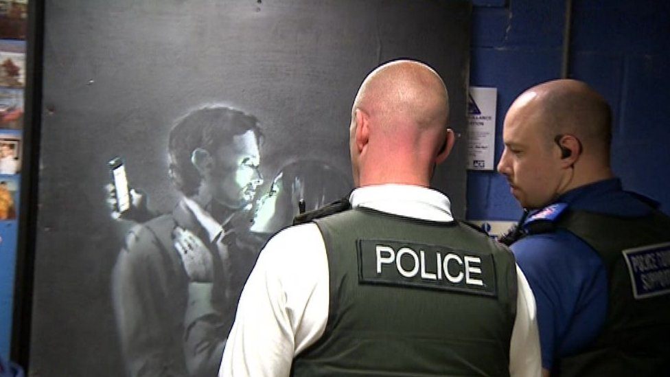 Police officers viewing the Banksy artwork