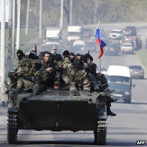 Men in military fatigues ride on an APC in Kramatorsk