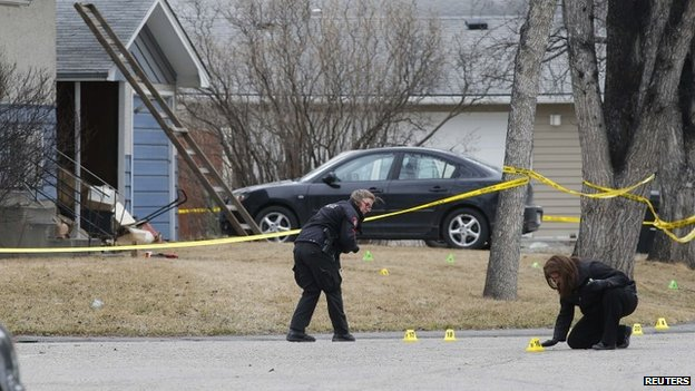 Police officers mark and photograph evidence at a house where five people were stabbed in the early morning hours in Calgary, Alberta, 15 April 2014