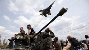 A fighter jet flies over Ukrainian soldiers on an armoured personnel carrier, Kramatorsk, Ukraine