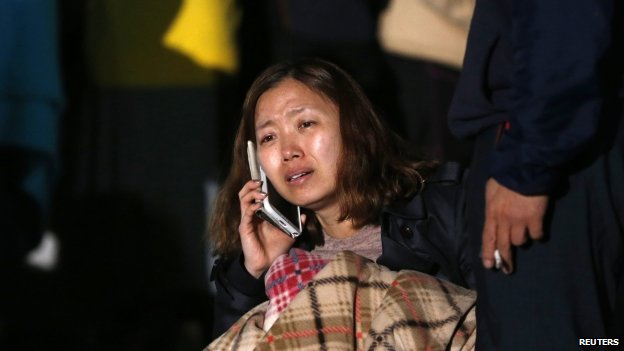 A family member of a missing passenger cries as she waits for a rescue team's arrival at a port where family members of missing passengers are gathered in Jindo, South Korea, 16 April 2014