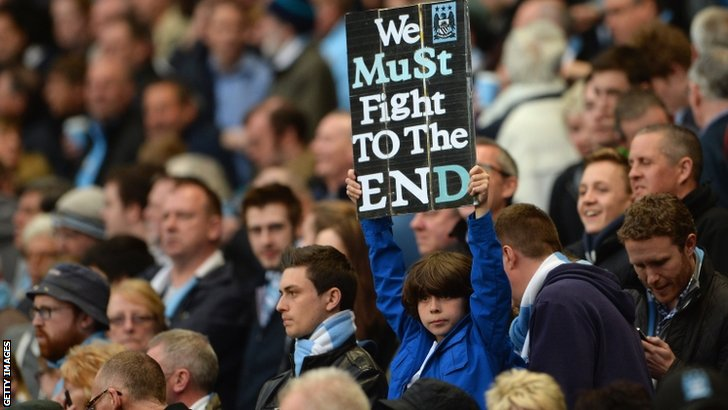 Fan holds up sign saying 'We must fight to the end'