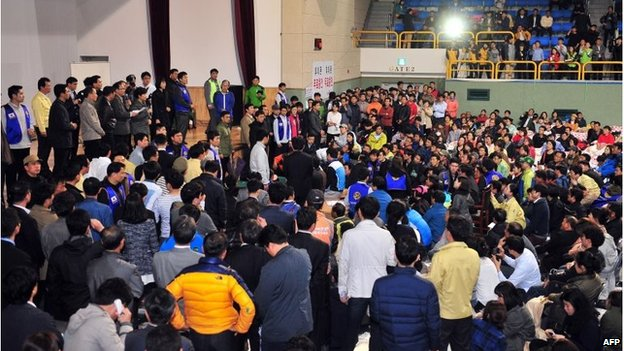South Korea's President Park Geun-Hye (left, on stage) addresses a hall full of relatives of missing passengers in Jindo