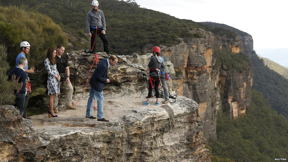 Prince William is looking over the edge of a cliff in Australia's Blue Mountains