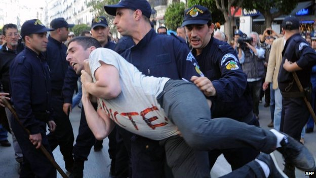 Algerian police arrest a protestor from the Barakat movement as they demonstrate in Algiers on 16 April 2014