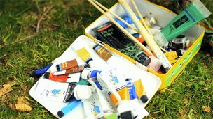 Acrylic paints in an art box lying on grass