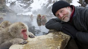 George McGavin beside a snow macaque in thermal pool