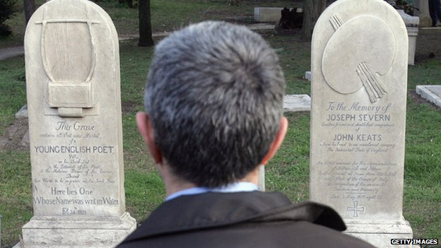 A man reads the epitaph on the graves of Keats and Shelley
