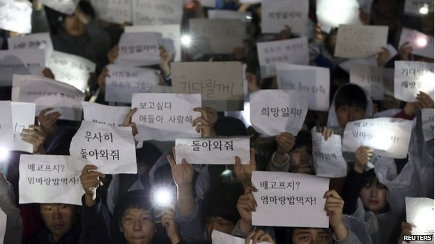 Students hold signs with messages of hope for the return of their missing friends who were on the Sewol ferry, which sank in the sea off Jindo, at Danwon High School in Ansan on 17 April 2014