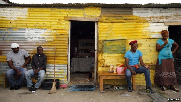 Members of a mining community sit outside their shacks in Nkaneng township in Rustenburg, South Africa, on 1 April 2014
