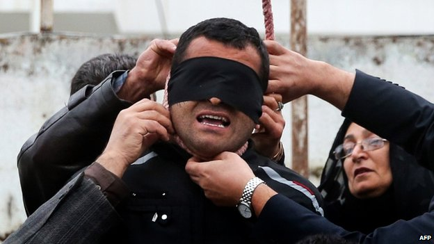 The mother (R) of Abdollah Hosseinzadeh removes the noose from around the neck of Balal, who killed her son, on 15 April 2014