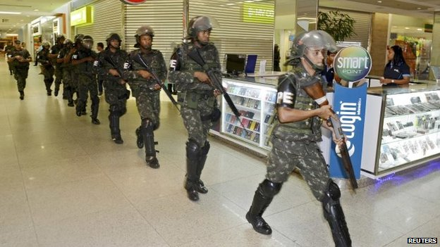 Soldiers patrol a shopping centre during a police strike in Salvador, Bahia state, April 17, 2014.
