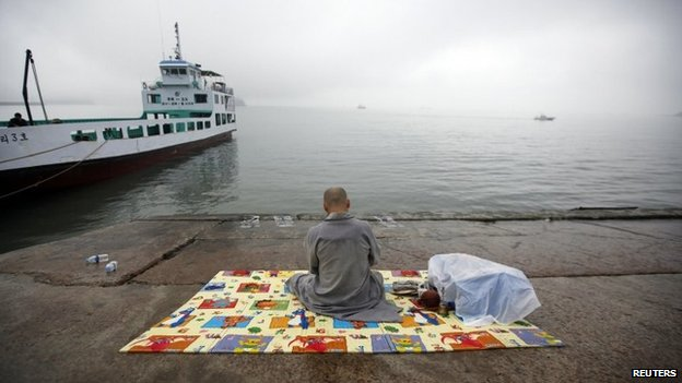 "A Buddhist monk prays for missing passengers who were on the South Korean ferry ""Sewol"" which sank in the sea off Jindo at a port where family members of missing passengers gathered in Jindo on 18 April 2014"