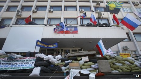 Masked pro-Russian protesters stand behind a barricade in front of the city hall as flags meant to represent the Donetsk Republic fly alongside Russian flags in Mariupol, Ukraine, Thursday, April 17, 2014.