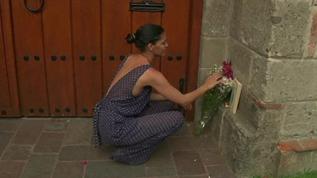 A woman lays flowers in memory of Gabriel Garcia Marquez