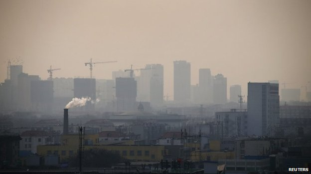 Smoke rises from a chimney among houses as new high-rise residential buildings are seen under construction on a hazy day in Tangshan, Hebei province, on 18 February 2014