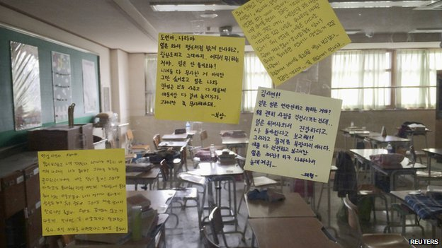 Messages left by fellow students are stuck to the classroom windows of students missing in the South Korean ferry disaster at Danwon High School in Ansan on 18 April 2014.