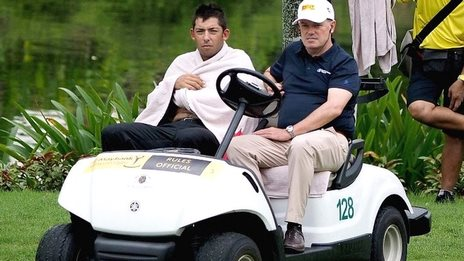 Pablo Larrazabal (left) is driven away from the lake by a Tour official