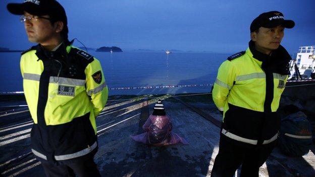 Член семьи пропавших пассажиров (C) наблюдает за место аварии, как полицейские стоят на страже в порту в Jindo 18 апреля 2014 года.
