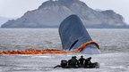 Vessel involved in salvage operations passes near the upturned South Korean ferry 'Sewol' in the sea off Jindo