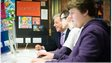 John Bercow looking at a computer screen alongside two young people