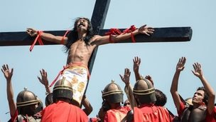 A Catholic devotee nailed to a cross is hoisted by participants dressed in soldier wear during a re-enactment of the crucifixion of Christ in Pampanga province, Philippines (18 April 2014)