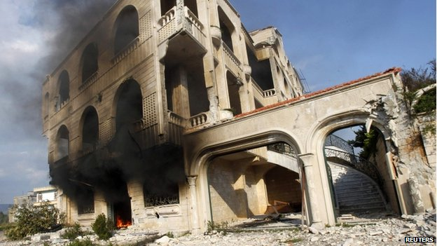 Fire burns in a damaged building in Homs (21 March 2014)