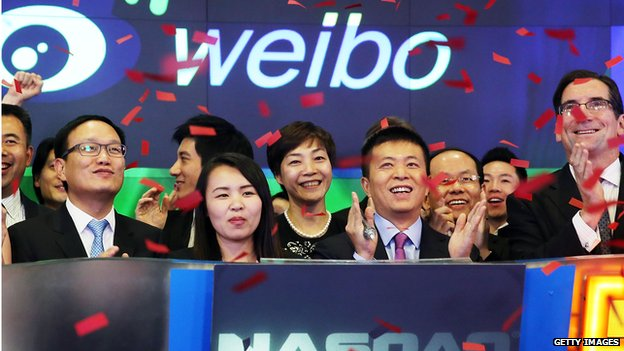 Weibo CEO Charles Chao (centre) stands with Robert Greifeld, Nasdaq CEO, moments after Weibo began trading on the Nasdaq exchange