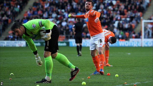 Blackpool caretaker player-manager Barry Ferguson clears tennis balls from the pitch