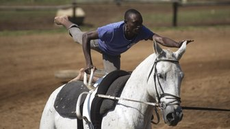 A Soweto resident balancing on a horse, South Africa - Tuesday 15 April 2014