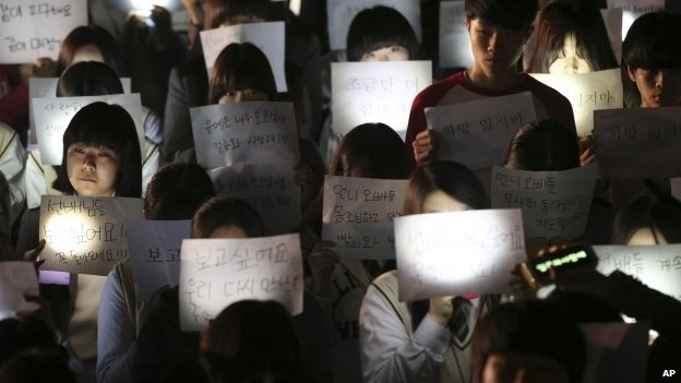 Students hold papers with candles as they pray for the safe return of their friends aboard the sunken ferry Sewol at Danwon High School in Ansan, south of Seoul, South Korea, Friday, April 18, 2014