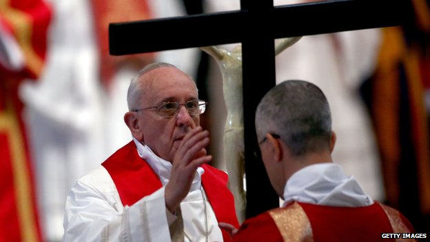 "Pope Francis kisses the cross as he attends a Papal Mass with the Celebration of the Lord's Passion inside St Peter""s Basilica on April 18"