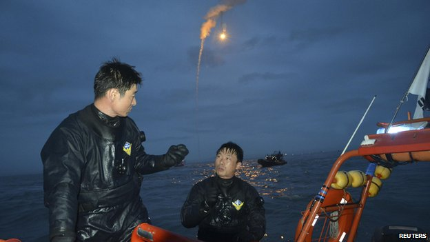 "Search and rescue workers operate near the area where passenger ship ""Sewol"" capsized off Jindo as lighting flares are released in the sky during a night search on April 18"