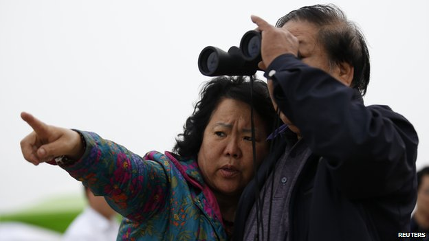 Song and his wife, whose granddaughter was on South Korean ferry Sewol which sank in the sea off Jindo and has been missing, look at the sea with a pair of binoculars in Jindo 19 April