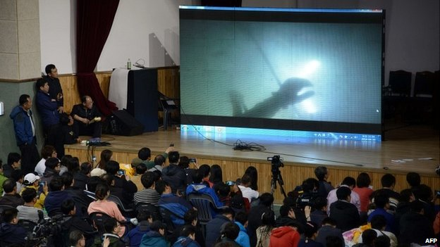 Relatives watch underwater footage of divers reaching the the sunken South Korean ferry - 19 April 2014