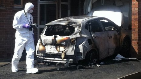 A forensic officer examines one of the cars damaged in the arson attack