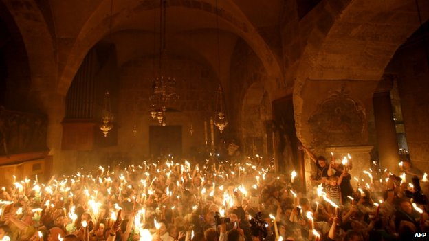 Christian pilgrims hold candles inside the Church of the Holy Sepulchre (19 April 2014)