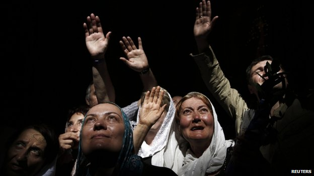Worshippers react to a beam of sunlight filtering from the ceiling inside the Church of the Holy Sepulcre (19 April 2014)